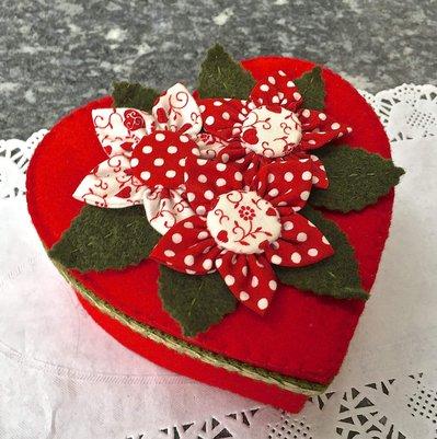 Scatola a forma di cuore rivestita in feltro rosso e decorata con fiori in tessuto rosso e bianco