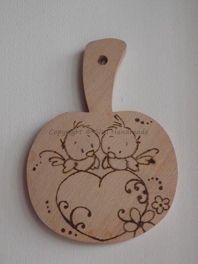 Tagliere a forma di mela in legno con teneri uccellini su cuore disegnati con pirografo