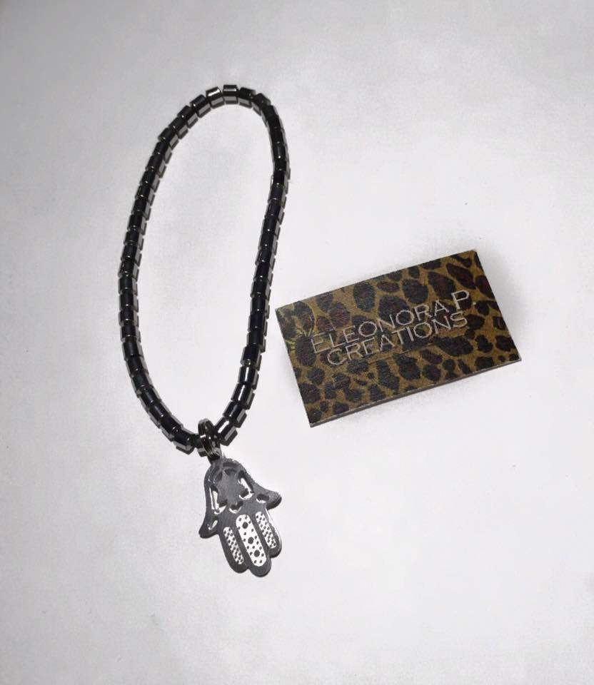 Bracciale elasticizzato con pietre ematite cilindriche e ciondolo mano di Fatima in acciaio