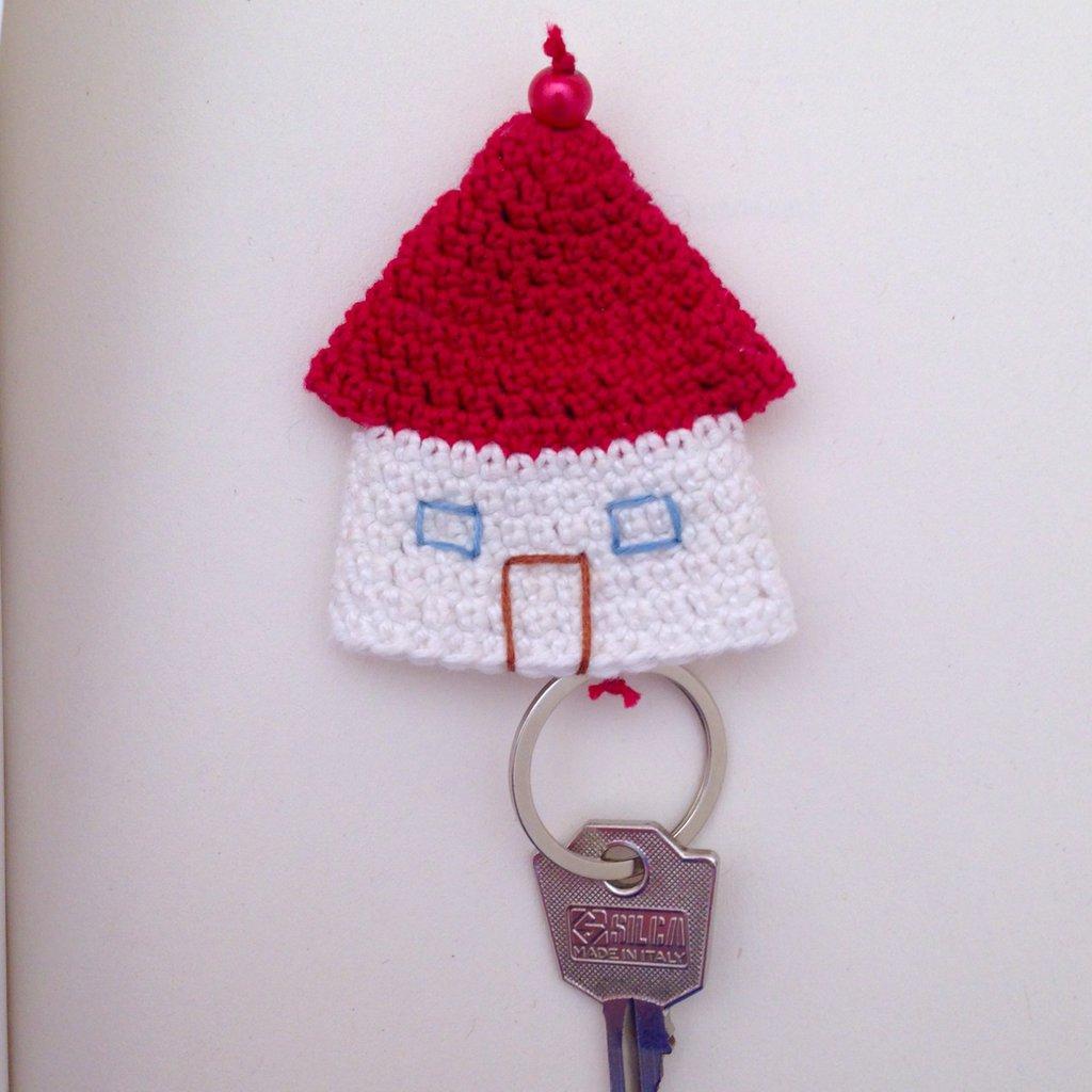 Portachiavi con casetta bianca e rossa con finestre e porta, fatta a mano all'uncinetto, con chiave a scomparsa