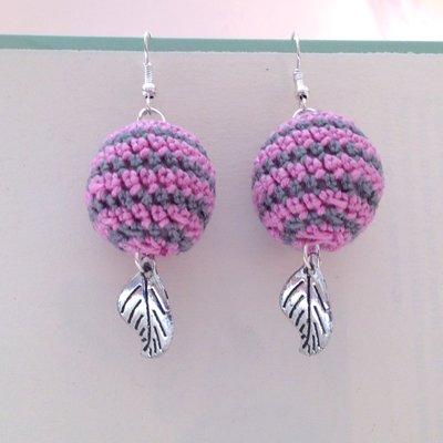 Orecchini pendenti con palline amigurumi a righe rosa e grigie, fatti a mano all'uncinetto, con ciondoli a foglia