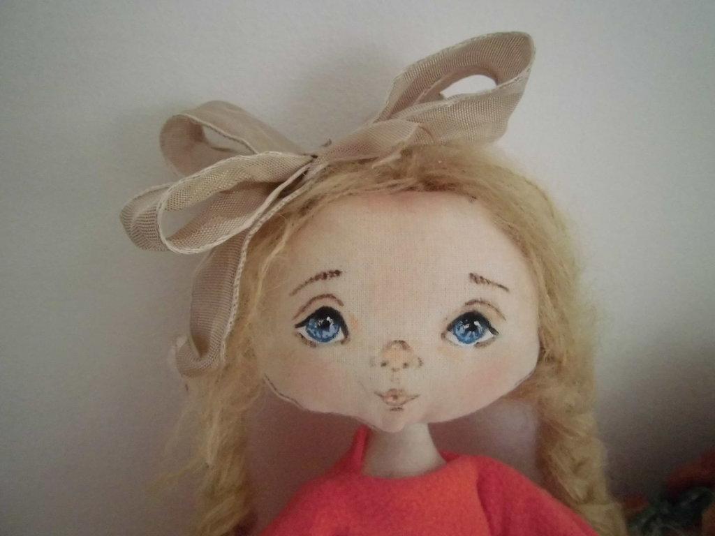 Bambola di stoffa dai biondi capelli ed occhi azzurri