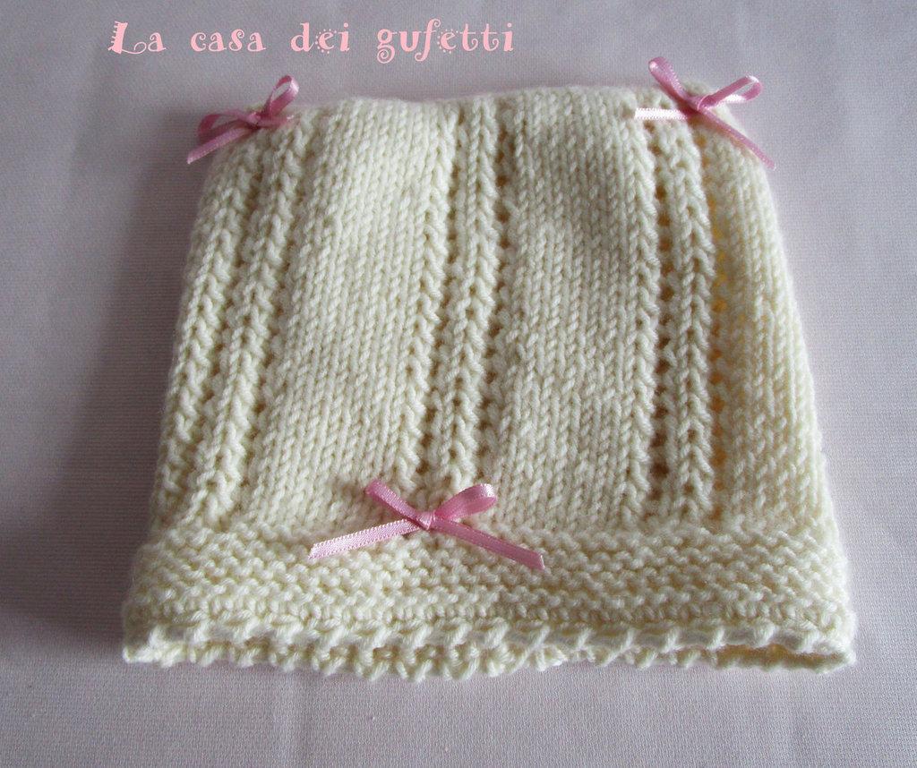 Cappellino in lana merinos panna con motivo traforato e fiocchi in raso rosa