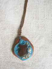 Collana con pendente in legno, vetro, cordoncino azzurro, sassolini e conchigliette.