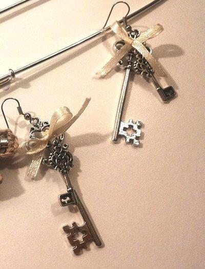 Orecchini vintage con due tipi di chiavina in metallo brunito e fiocchino in raso avorio
