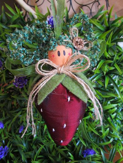 Bambolina a forma di fragola in stoffa di raso colorata con fiocchi e testina in legno