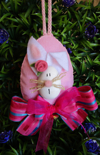 Uovo in feltro rosa imbottito con coniglietto in legno e fiocchi colorati
