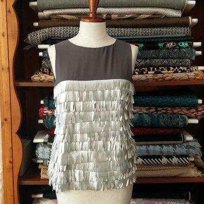 Sotto giacca smanicato in seta grigia con frange in ecopelle argento