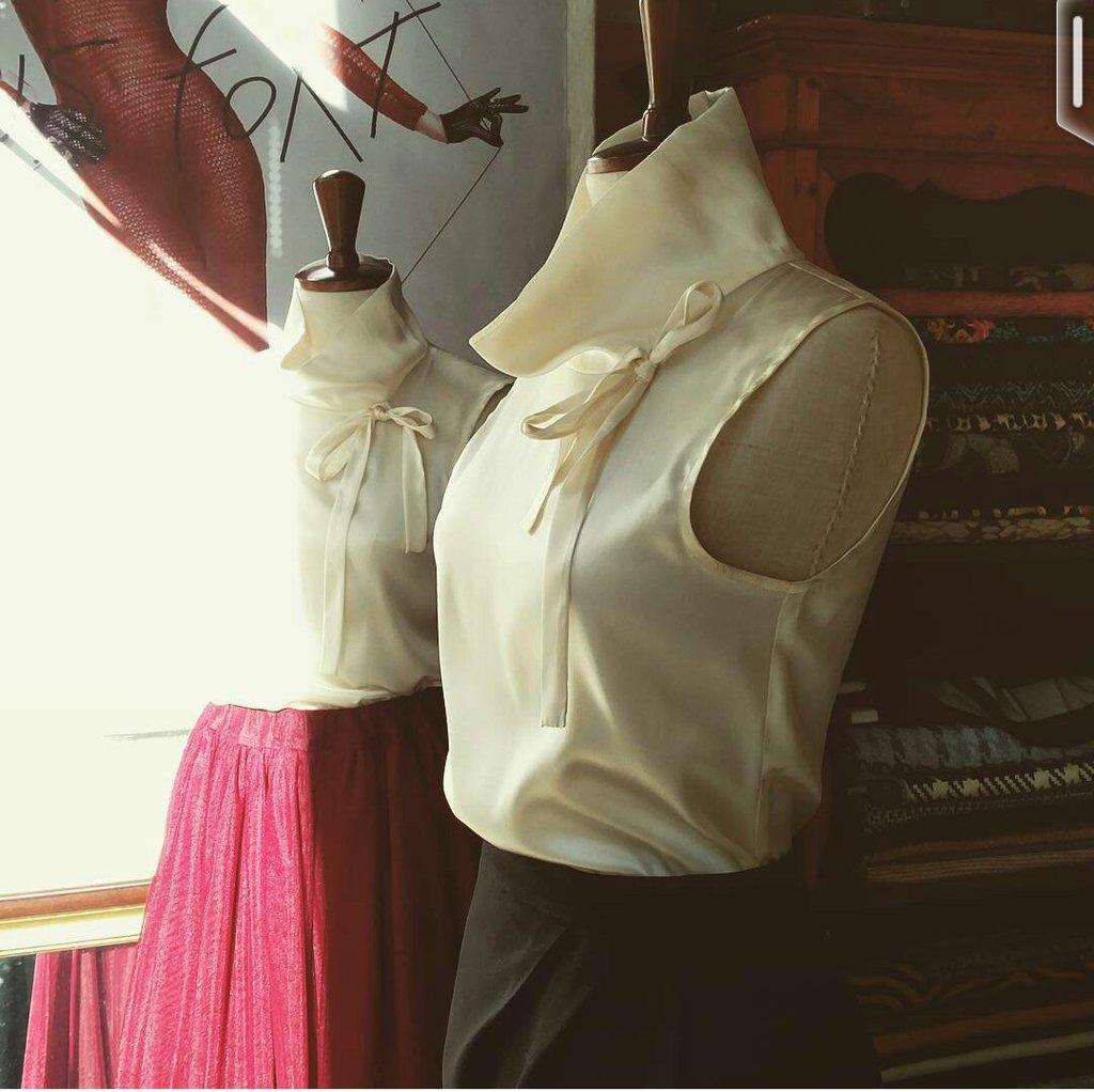 Sotto giacca smanicato in seta color crema con collo alto