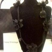 Collana lunga nera con fiori.