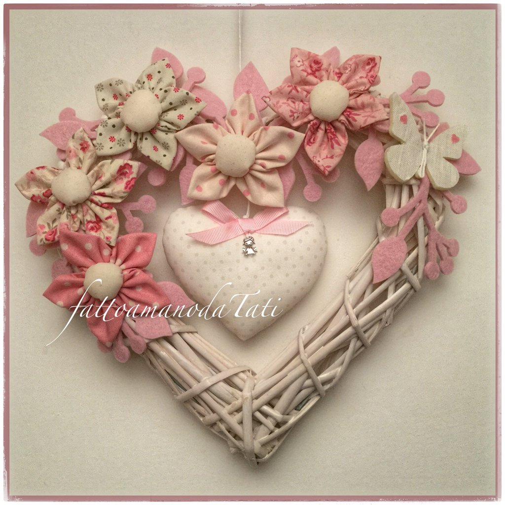 Cuore/fiocco nascita in vimini con 5 fiori in cotone sui toni del rosa e beige ,farfalla e cuore centrale
