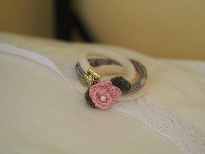 Bracciale in lana tubolare.3 fili color crema/beige.Fiore centrale ( rosa),con foglie (uncinetto) ,perla e ciondolo in metallo (farfalla)
