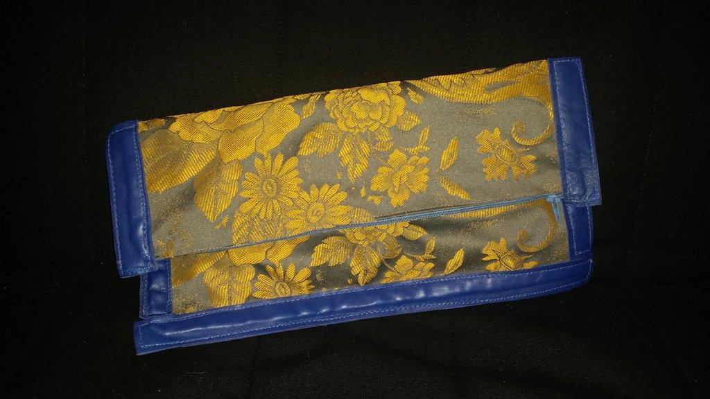 Pochette elegante in stoffa con profili in pelle