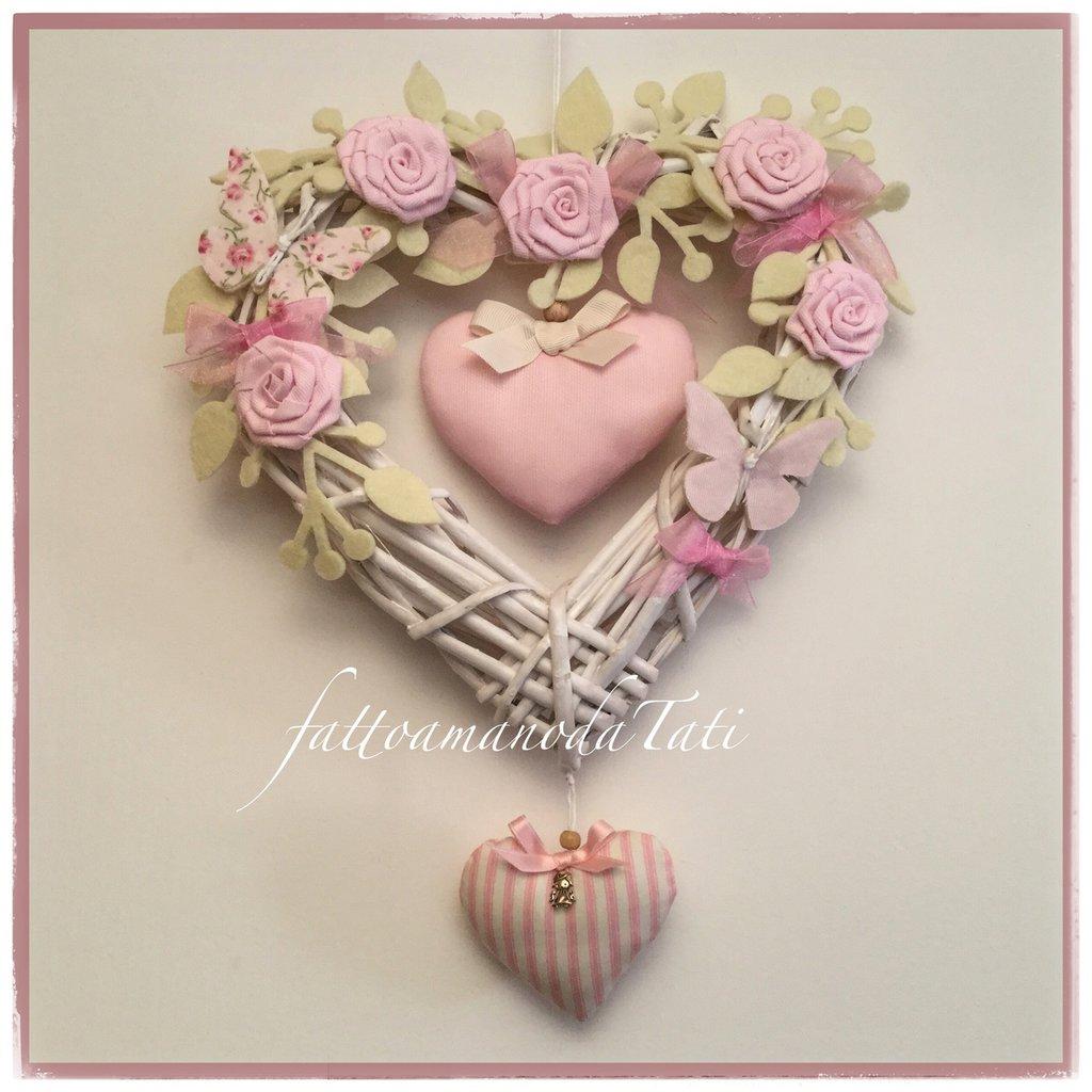Cuore/fiocco nascita in vimini con roselline,farfalle e due cuori sui toni del rosa