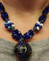Collana con ciondolo etnico e gruppi di perline a nodi  sul blu