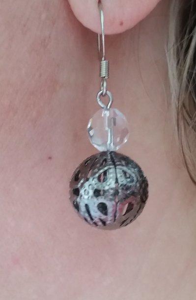 Orecchini pendenti con pallina metallica traforata e mezzo cristallo trasparente