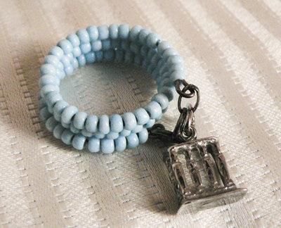 Anello di perline in porcellana con ciondolo in argento rodiato.