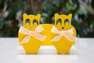 Portatovaglioli in legno fatti a mano con sagome decorative di gufi gialli.