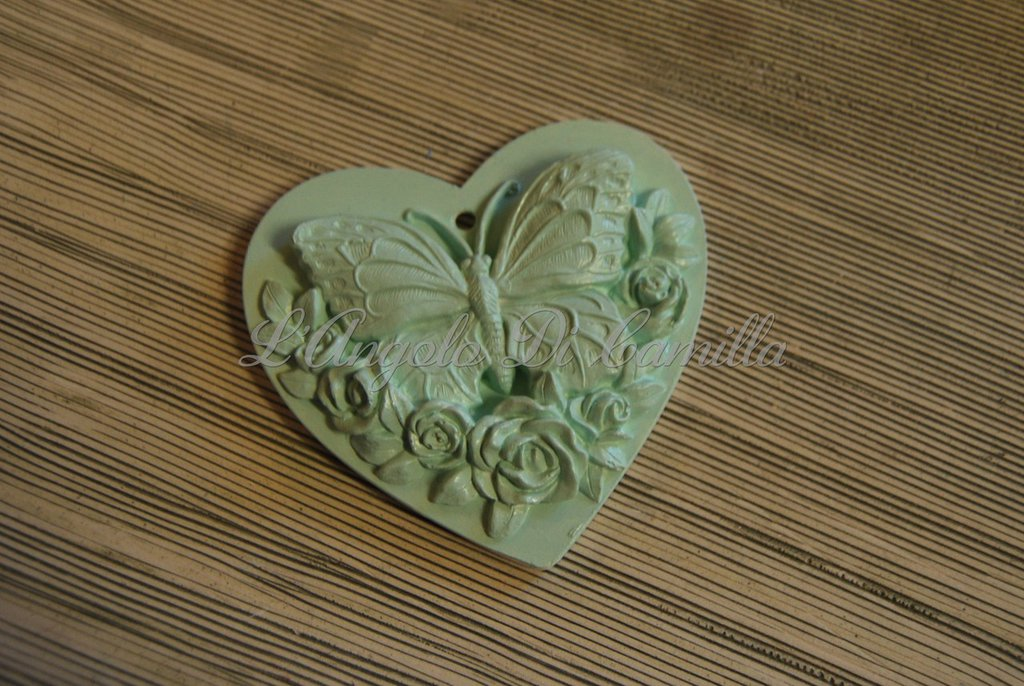 Cuore in gesso con farfalla e fiori