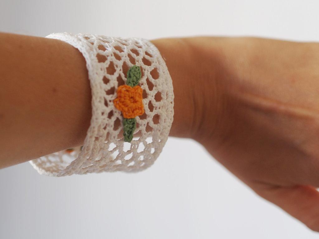 Bracciale di cotone bianco,in pizzo all'uncinetto.Applicazione di fiori e foglie a contrasto (arancione),chiuso da un bottone.Indurito per facilitare il modo di indossarlo.A richiesta varianti.