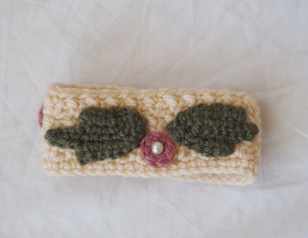 Bracciale a fascia in maglia di lana.Applicati 3fiori ,3foglie e 3perle .(beige con fiori ciclamino e foglie salvia).Personalizzabile-Lavorazione uncinetto.