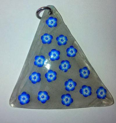 ciondolo in gel uv triangolare base semitrasparente con fiori blu'e bianchi in fimo