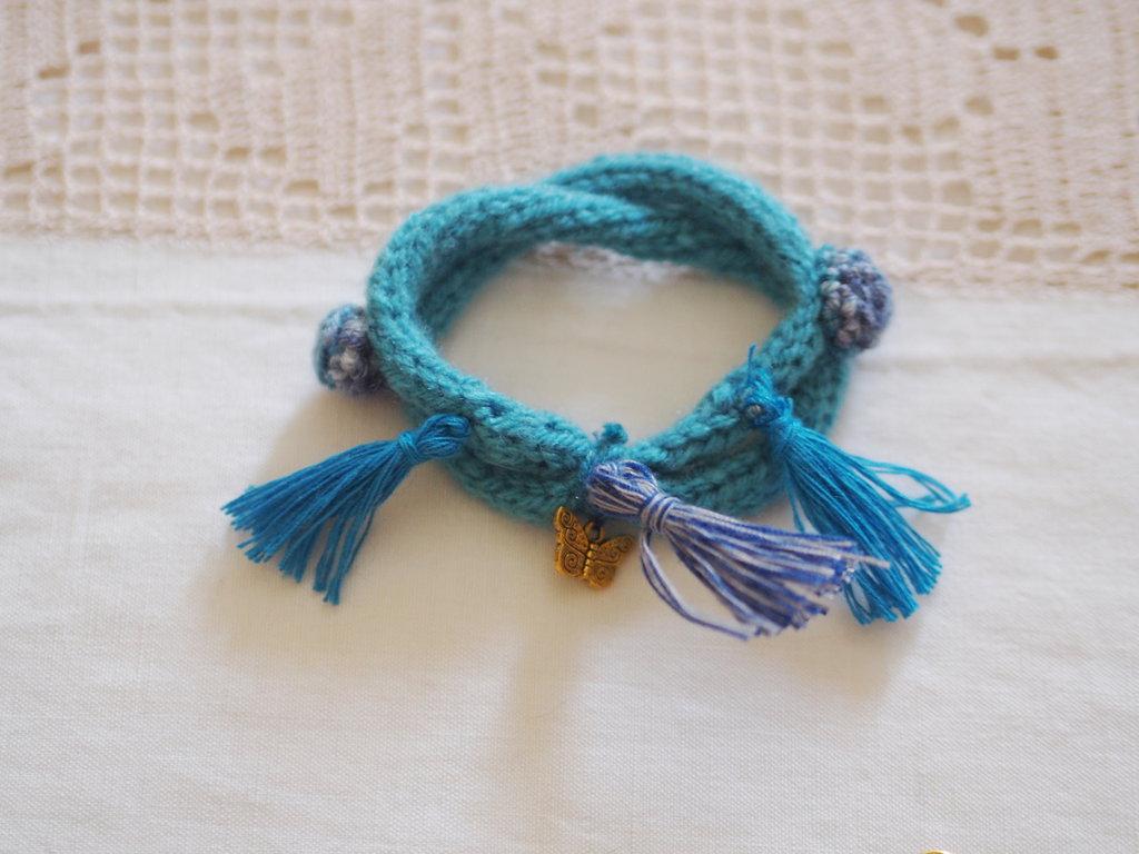 BRACCIALE Turchese e blu mèlange in maglia di lana tubolare.Due giri intrecciati con applicate 2roselline mèlange e 3nappine.Ciondolo :farfalla.(Della parure 4 pz.in vendita)