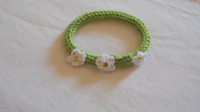 Bracciale in maglia di lana verde prato,tubolare.Inserite 3 margherite in cotone bianco(uncinetto)e perline gialle.Parte di una parure