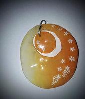 ciondolo in gel uv fatto a mano con forma ovale con inserto centrale colorato con sfumature che vanno dal bianco all'arancio con anello e cordoncino