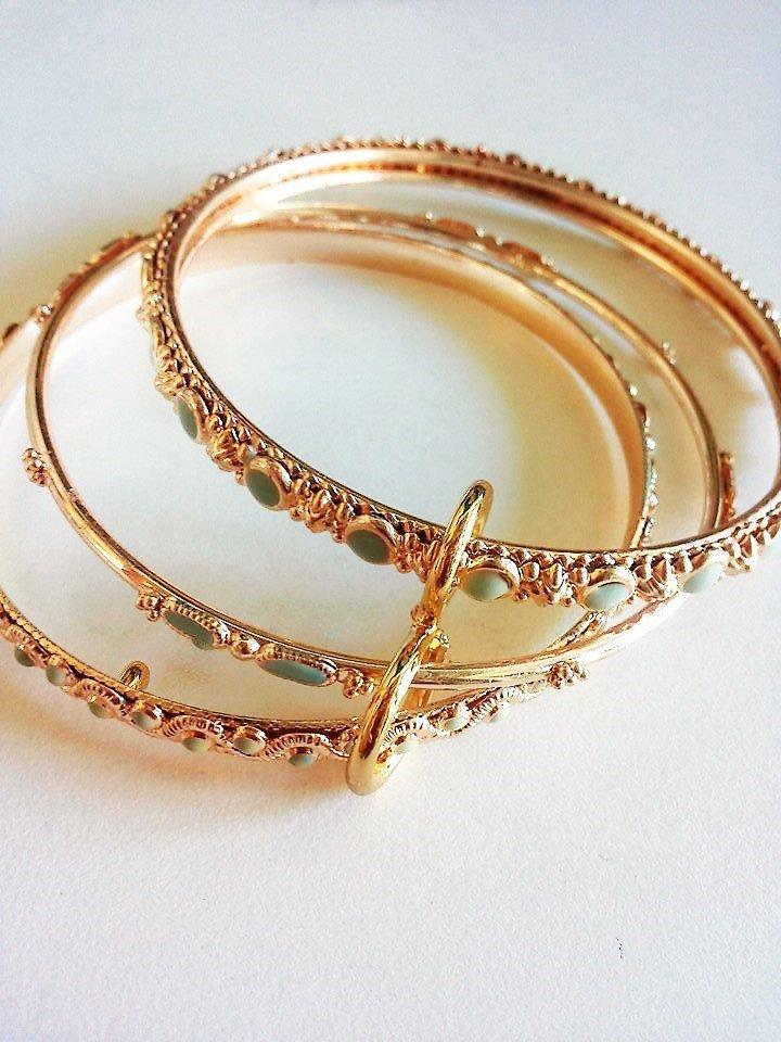 Tris bracciali rigidi metallo dorato con incastonate piccole pietre celesti di forme e dimensioni varie