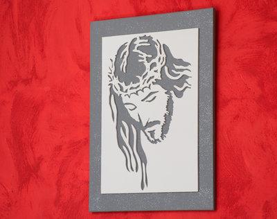 Quadro in legno Gesù Cristo, realizzato a mano utilizzando la tecnica del traforo, immagine di colore bianco su sfondo grigio brillantino.