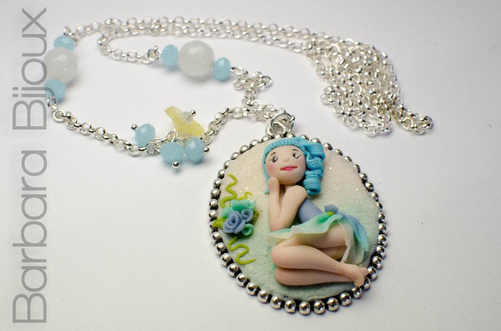 Collana lunga con doll / bambolina dei fiori dai toni dell' azzurro su cammeo.