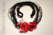Collana realizzata a mano in cordone cerato nero con fiori rossi all'uncinetto e perline indiane e perle di plastica.