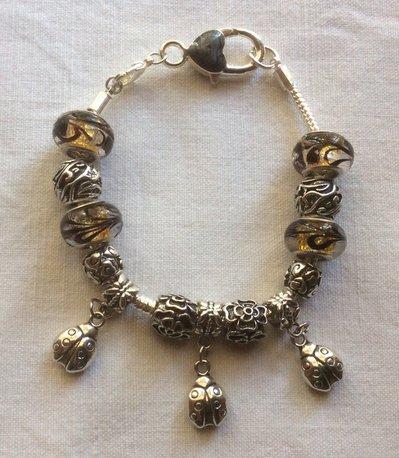Stupendo bracciale in argento tibetano e vetro di Murano con portafortuna