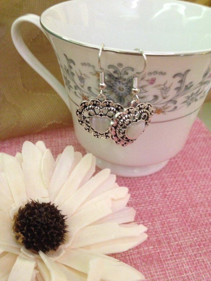 orecchini pendenti in metallo decorati con pietra bianca centrale e strass.