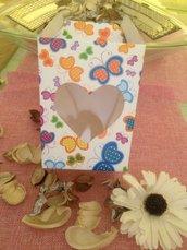 scatola bianca con farfalle colorate e con cuore traparente