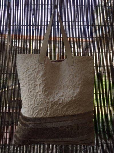 Borsa con manici rigidi di colore chiaro, base in tessuto vellutato a strisce e tessuto superiore di colore chiaro con disegni in rilievo