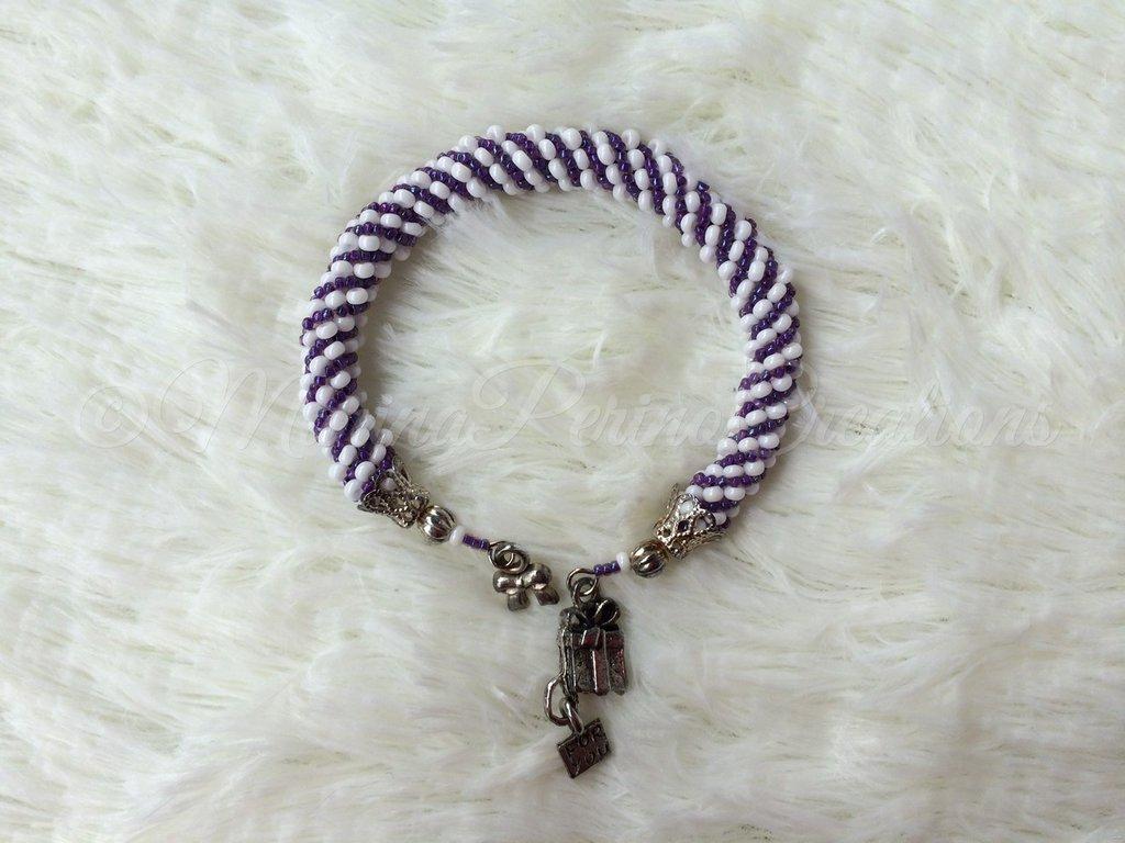 Bracciale di perline creato con la spirale russa, colori viola e bianco. Metallo color argento
