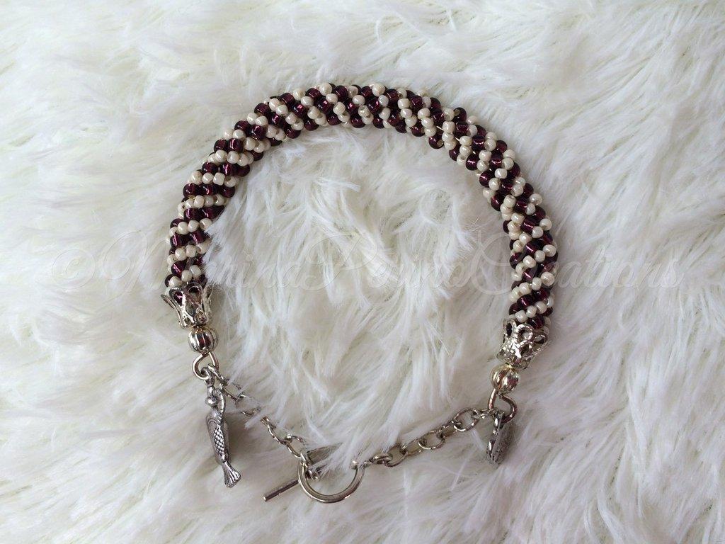 Bracciale di perline creato con la spirale russa, colori viola e beige. Metallo color argento