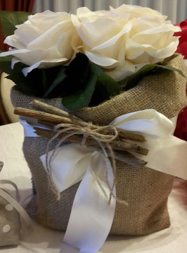 Contenitore portafiori realizzato a mano con tessuto tipo sacco, fiocco in raso  e sei rose in tessuto avorio.
