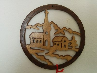Paesaggio innevato con chiesa, casa, albero e montagne, realizzato con la tecnica del traforo