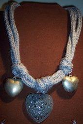 Collana in lana carta da zucchero con cuori in metallo e resina.