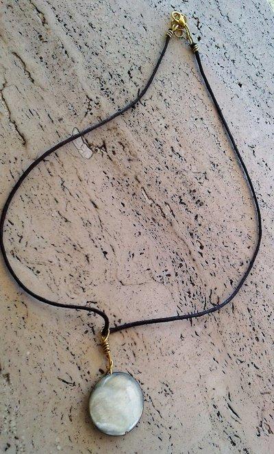 Collana corta con pietra piatta tonda grigio sfumato, montatura di ottone e filo in cuoio