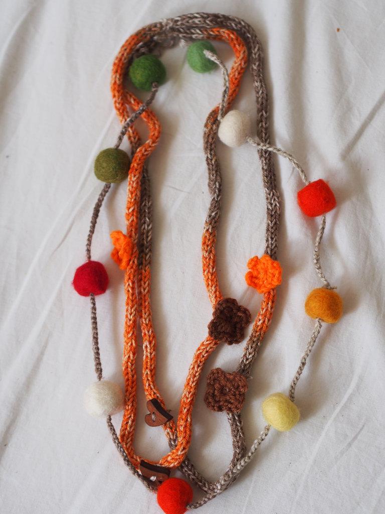 Collana in maglia tubolare.2 fili scalari(lana-seta-cotone)4 fiori a crochet(arancio-marrone).Bottoni a cuore (legno)Filo di palline in feltro in tinta