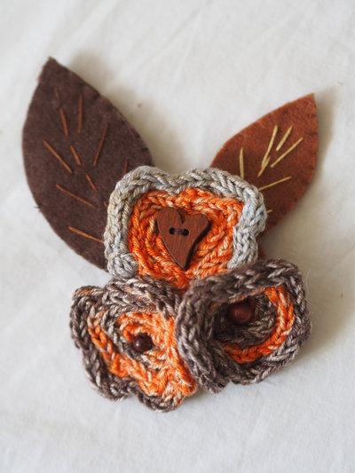 SPILLA in feltro e maglia tubolare.Arancione-beige-marrone -arancione(lana,seta,cotone).FIORI ,palline e cuore in legno.Foglie ricamate,in feltro.Gioiello/accessorio