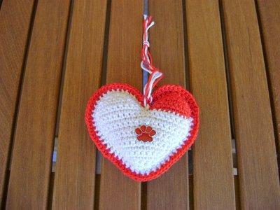 Cuori Amigurumi all'uncinetto, in 100% cotone di colore rosso e bianco, con imbottitura in poliestere, e charms rosso a forma di orma di zampetta;