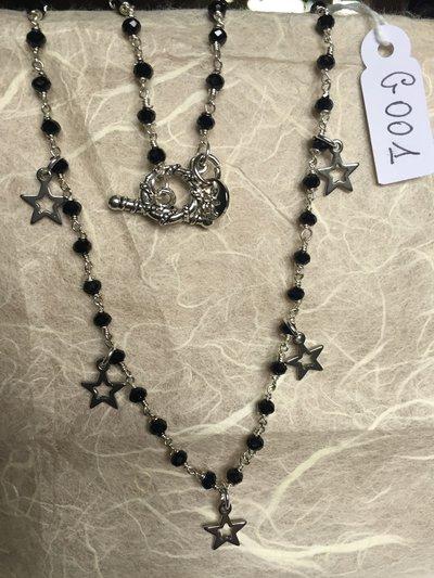Collana girocollo con perline di spinello nero e ciondoli in metallo a forma di stelle.