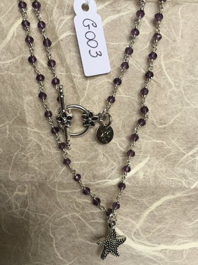 Collana girocollo con perline di ametista e ciondolo in metallo a forma di stella marina.
