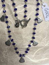 Collana girocollo con perline di agata blu e ciondoli in metallo a forma di cuore.