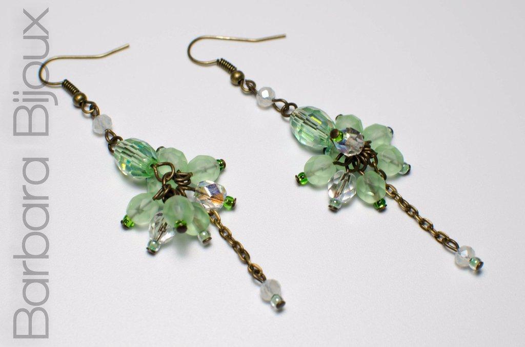 Orecchini pendenti con perle di vetro sul verde.